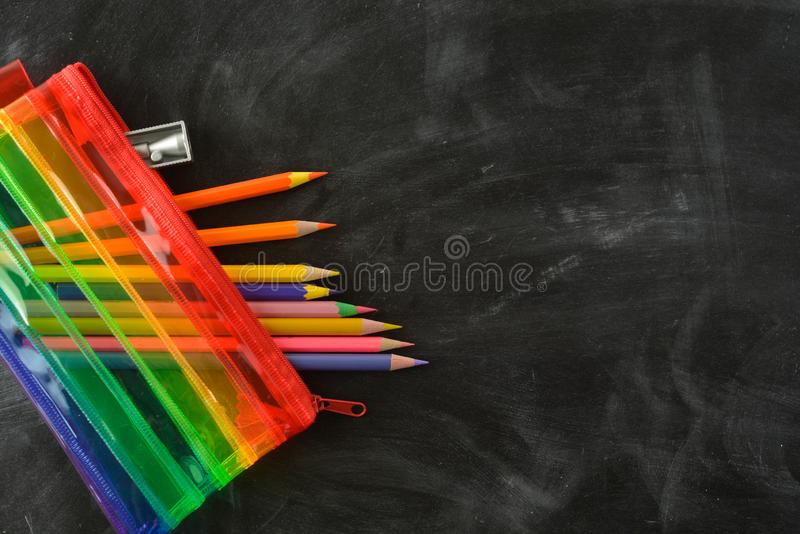 Back to school. Rainbow pencil case with school supplies for student. Black background. Copy space royalty free stock photography