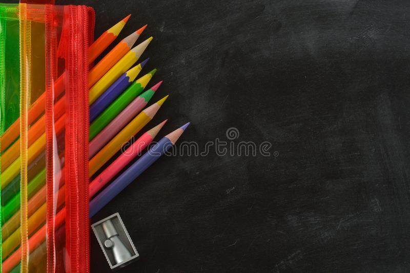 Back to school. Rainbow pencil case with school supplies for student. Black background. Copy space. Back to school. Rainbow pencil case with school supplies for stock photography