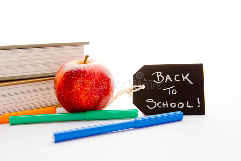 Back to School - Red Apple, books and pens. With blackboard handwritten chalk label royalty free stock image