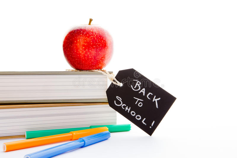 Back to School - Red Apple, books and pens. With blackboard handwritten chalk label royalty free stock images