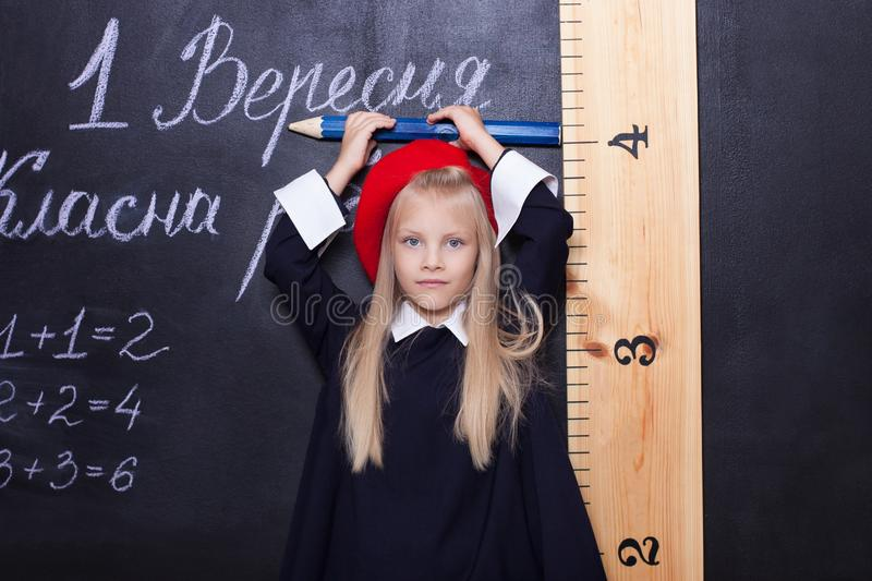 Back to school!Schoolgirl is at the blackboard with a ruler.Schoolgirl answers the lesson.First grader near the chalk board.The ki royalty free stock photography