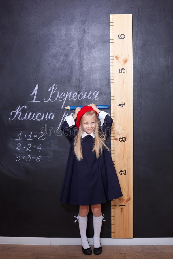 Back to school!Schoolgirl is at the blackboard with a ruler.Schoolgirl answers the lesson.First grader near the chalk board.The ki royalty free stock photos