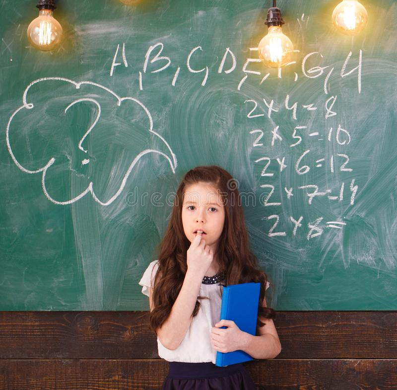 Back to school. Schoolgirl. School concept. Smiling little girl, writting text on blackboard. Little first graders. Back stock images