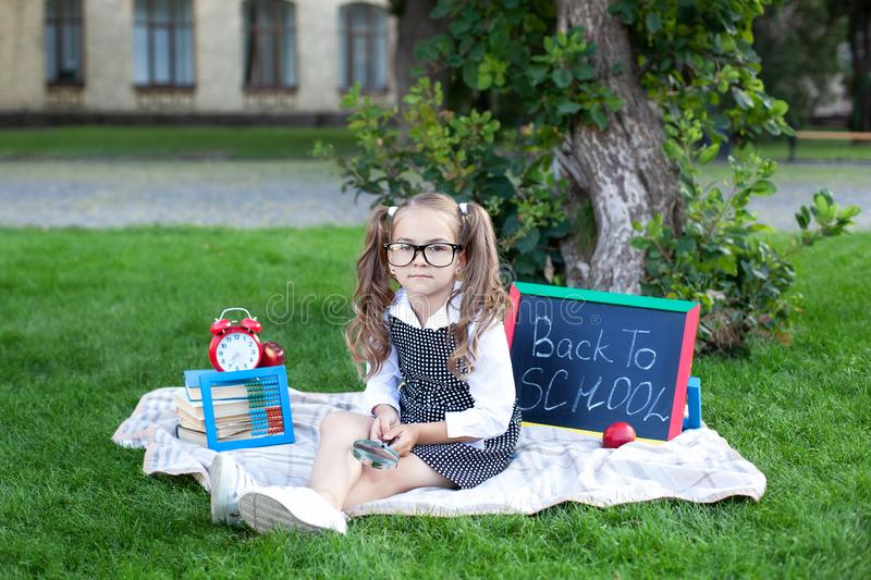 Back to school. schoolgirl with glasses holds a magnifying glass. A little girl sits on the grass near the school with books, a sc stock photos