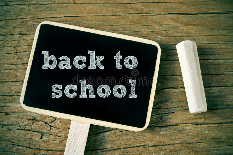Back to school. The sentence back to school written with chalk in a blackboard label, on a rustic wooden background royalty free stock photo