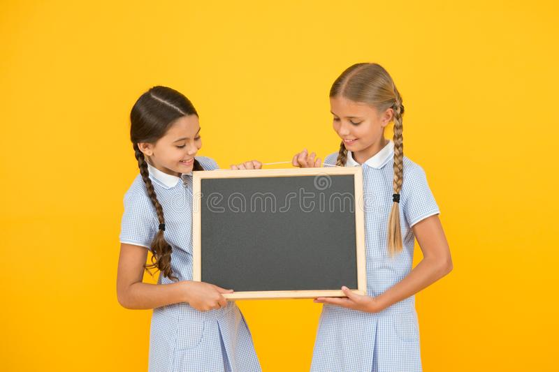 Back to school. small girls hold blackboard. children education. small girls presenting project. old school. copy space royalty free stock photo