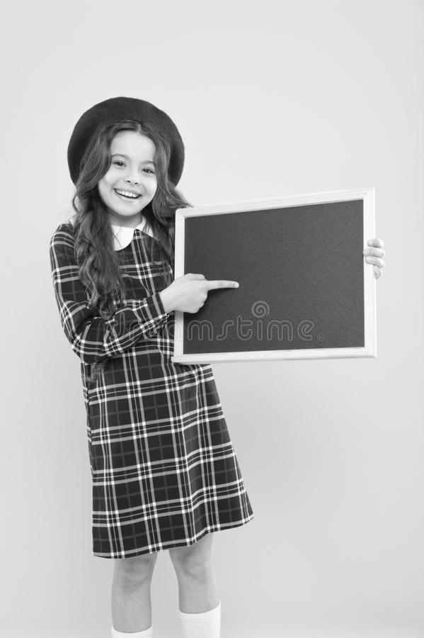 Back to school. Small school child pointing finger at blank blackboard on yellow background. Cute little schoolgirl with. Chalkboard on school day. Adorable stock image