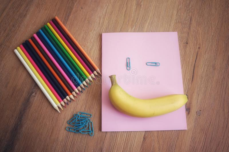 Back to school with a smile. School accessoires, colored pencils, paper clips, notebook, banana , smile on wooden background royalty free stock photos