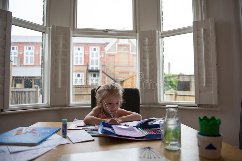 Back to School Soon 4. Little girl doing her class work at home to prepare for the coming school stock image