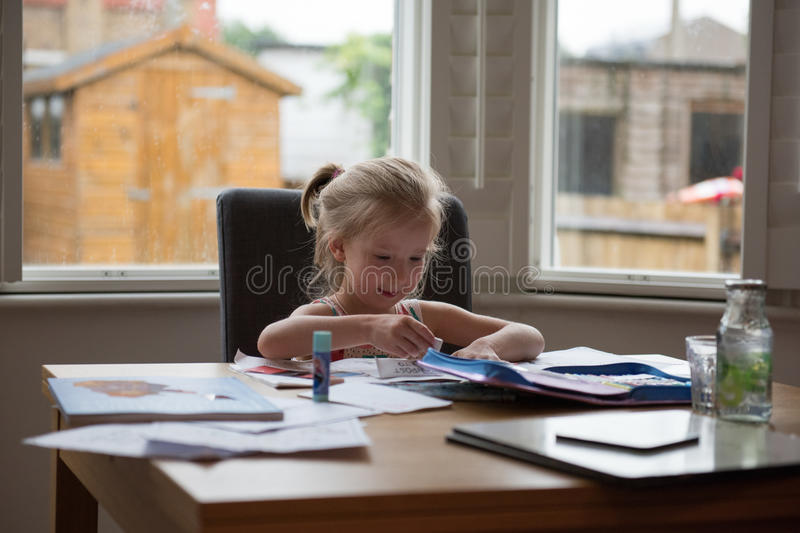 Back to School Soon 6. Little girl doing her class work at home to prepare for the coming school royalty free stock image