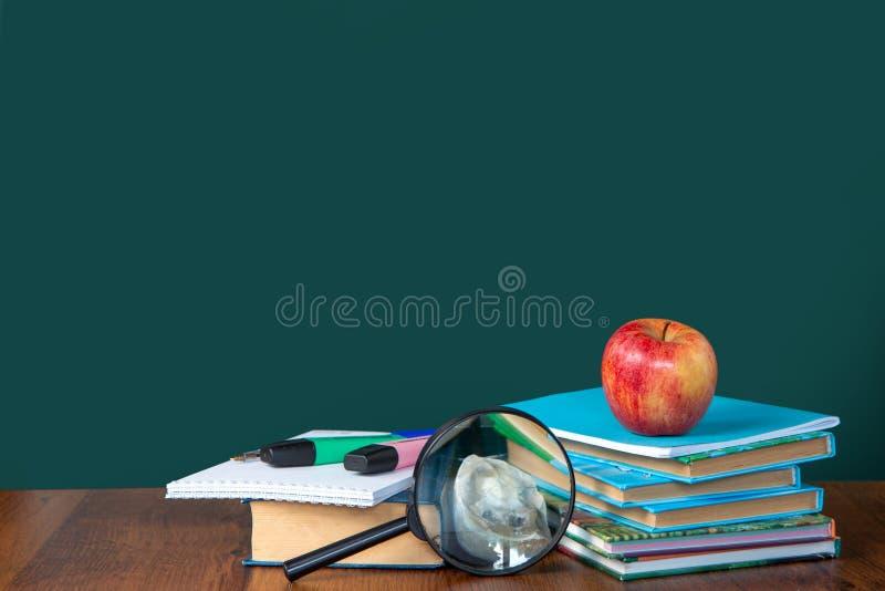 Back to school. Still life with school supplies. Blackboard in chalk chalkboard. Green background. Notebooks, notebooks, felt-tip. Pens, colored pencils stock image