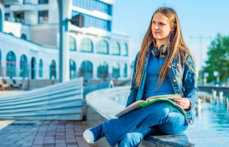 Back to school student teenager girl reads a textbook. Outdoor portrait of young teenager brunette girl with long hair. royalty free stock photo
