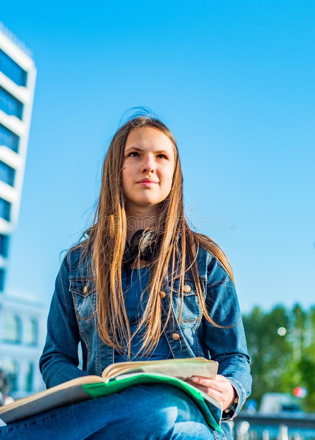 Back to school student teenager girl reads a textbook. Outdoor portrait of young teenager brunette girl with long hair. royalty free stock photography