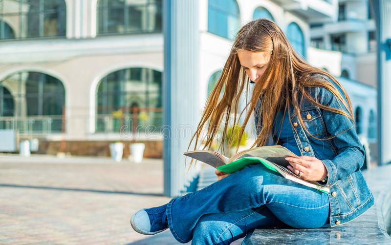 Back to school student teenager girl reads a textbook. Outdoor portrait of young teenager brunette girl with long hair. stock photography