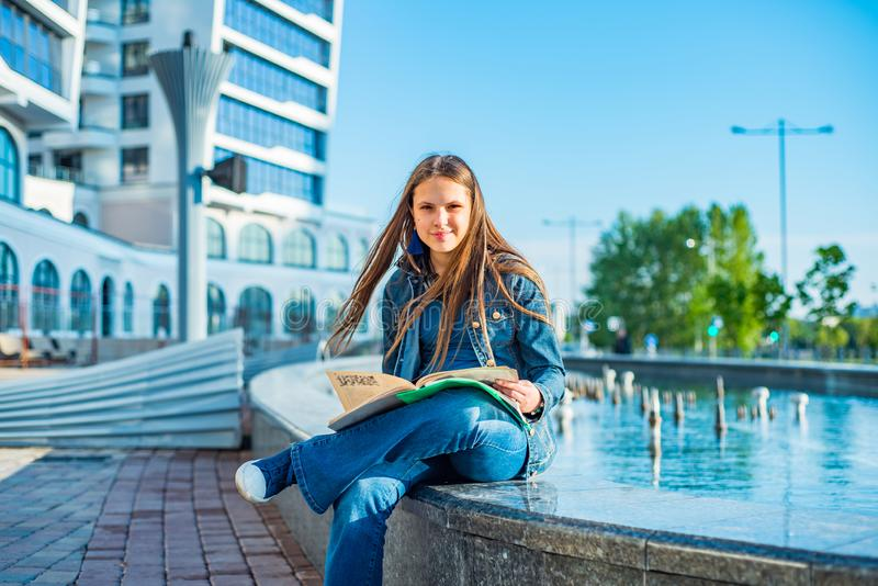 Back to school student teenager girl reads a textbook. Outdoor portrait of young teenager brunette girl with long hair. royalty free stock images