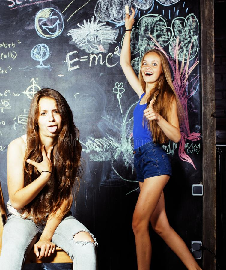Back to school after summer vacations, two teen girls in classroom with blackboard painted stock photos