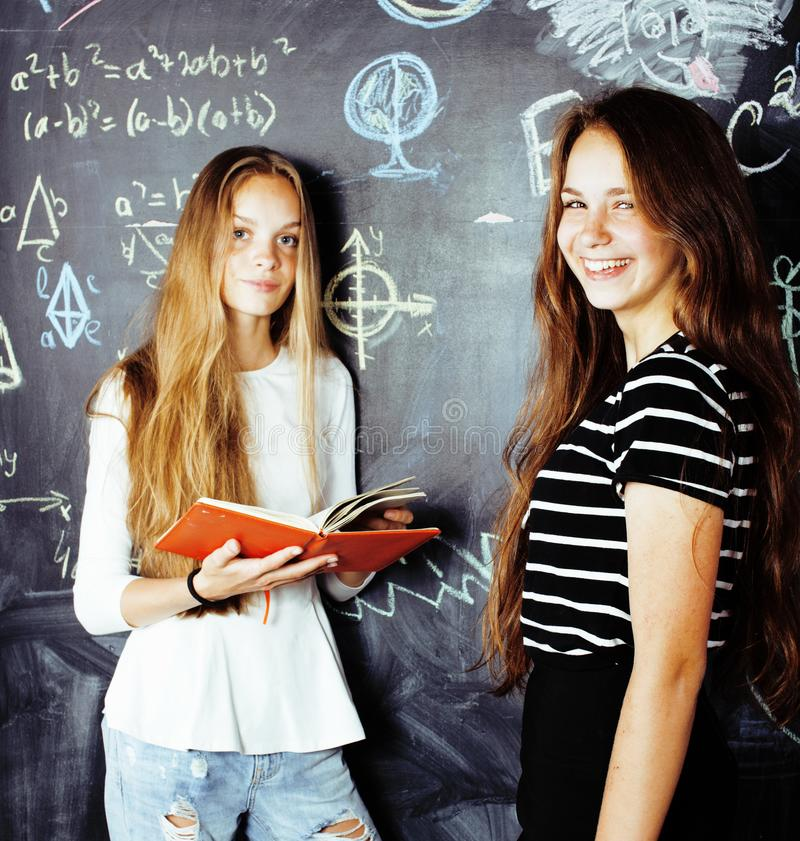Back to school after summer vacations, two teen girls in classroom with blackboard painted together royalty free stock photos
