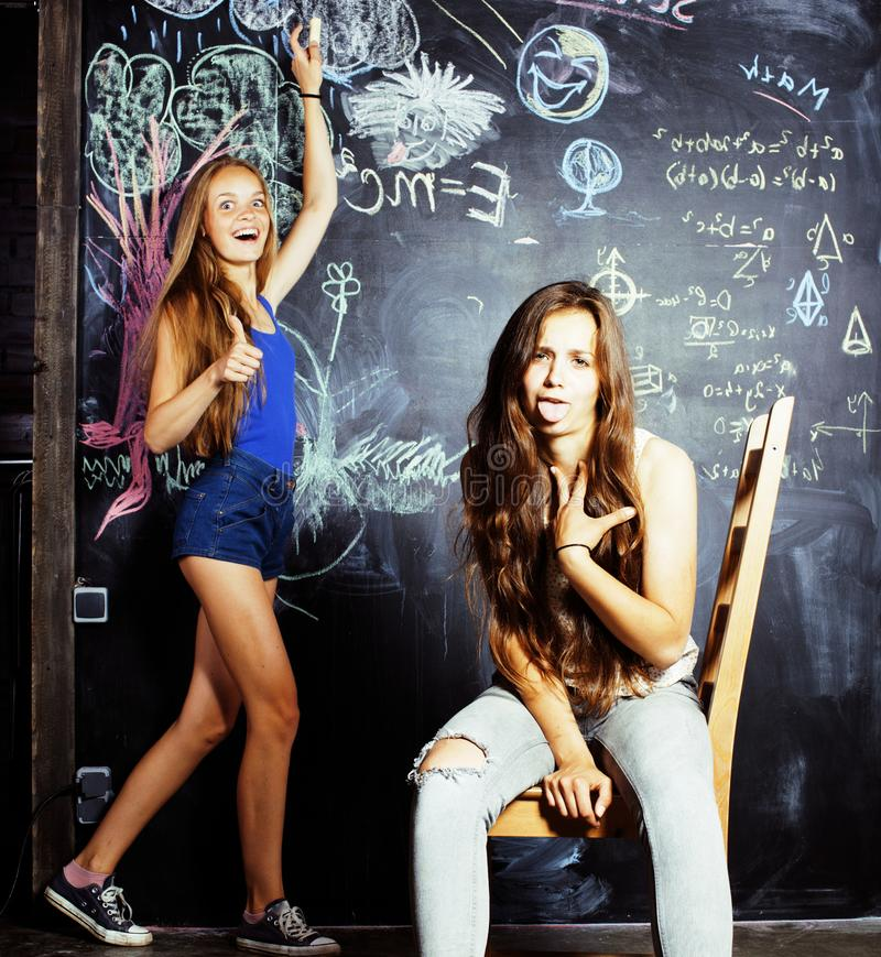 Back to school after summer vacations, two teen girls in classroom with blackboard painted stock photography