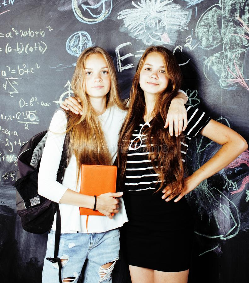 Back to school after summer vacations, two teen girls in classroom with blackboard painted together royalty free stock photography