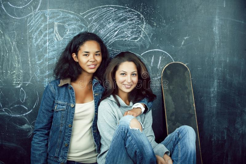 Back to school after summer vacations, two teen real girls in classroom with blackboard painted together, lifestyle. Mixed races people concept closeup royalty free stock image