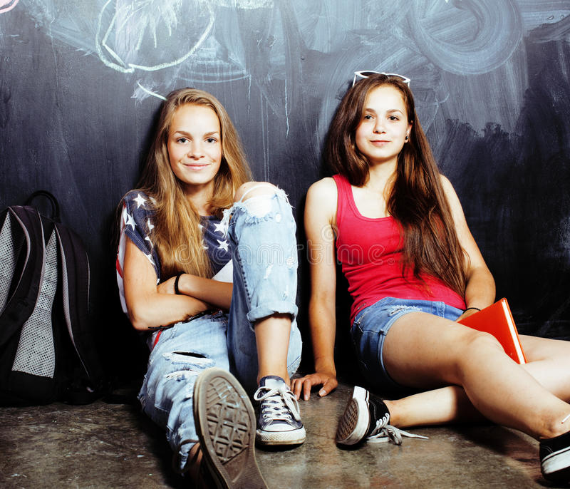 Back to school after summer vacations, two teen real girls in classroom with blackboard painted together, lifestyle. People concept close up royalty free stock photo