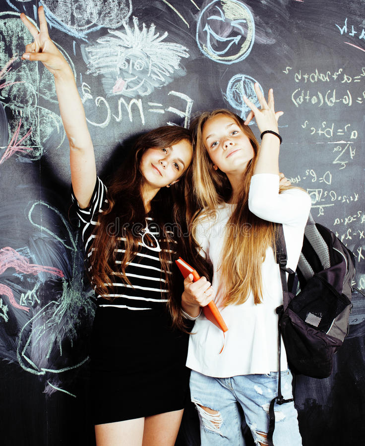 Back to school after summer vacations, two teen real girls in classroom with blackboard painted together, lifestyle. People concept close up stock photos