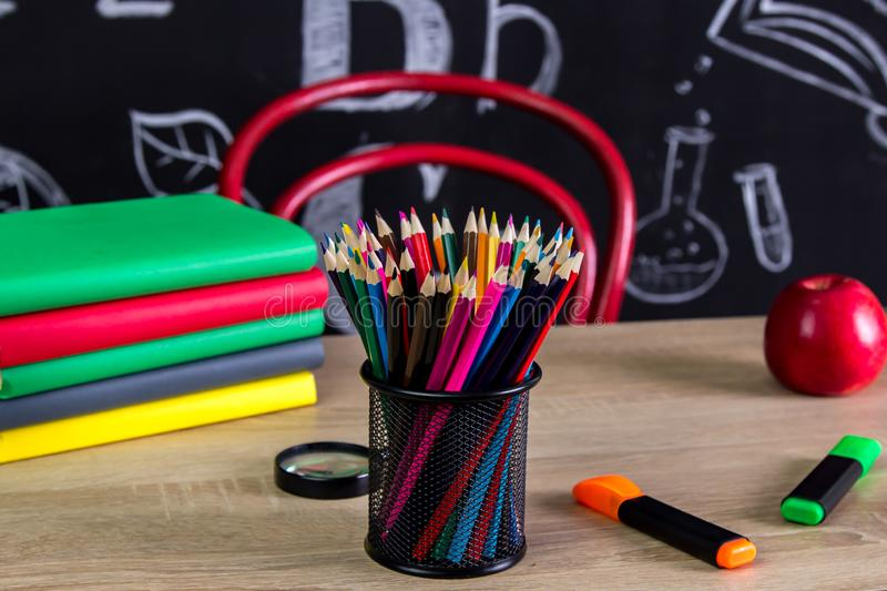 Back to school supplies. Books, felt-tip pens, magnifying glass, red apple and a chalkboard on the background stock photography