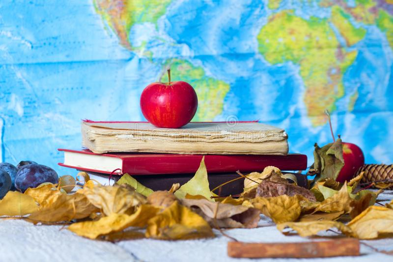 Back to school supplies. Books, geographic map and red apple on wooden table. stock photo