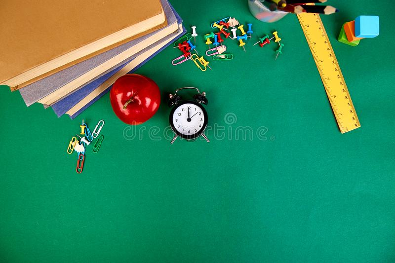 Back to school supplies. Books and red apple on green background royalty free stock photography