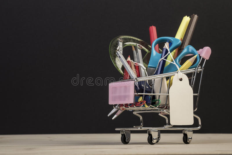 Back to school template with multiple stationery in trolley. With an empty label against black stock photography