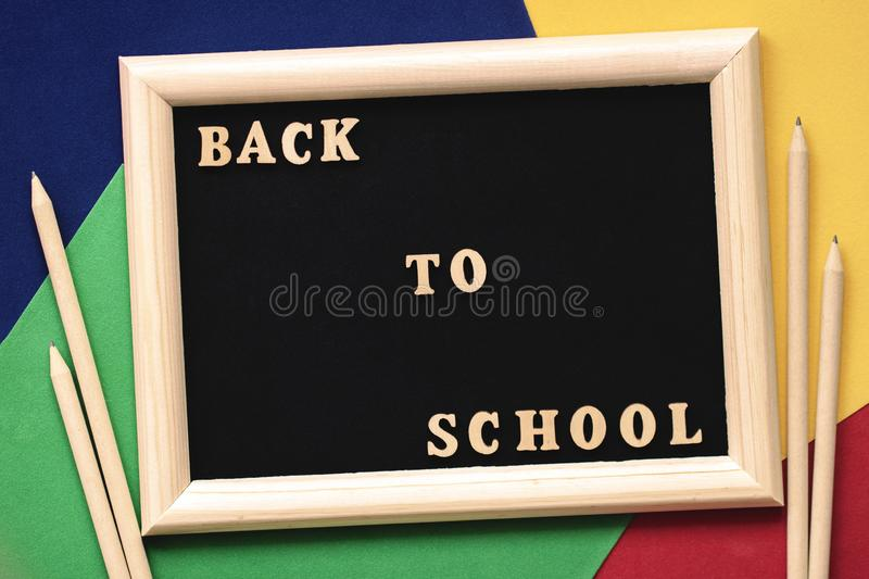 Back to school text, wooden letters in black background, frame on colored paper sheets, pencils. Concept of education royalty free stock images