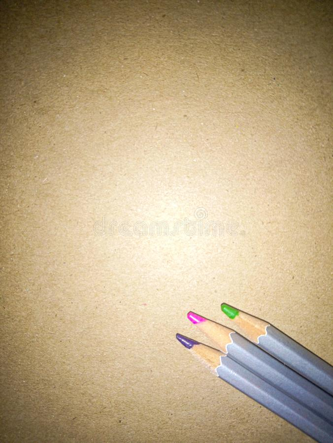 Back to school. Three pencil crayons against a plain cardboard background. royalty free stock image