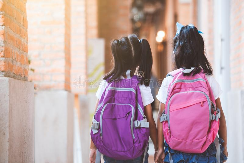 Two cute asian child girls with school bag holding hand and walk together in the school. Back to school. Two cute asian child girls with school bag holding hand royalty free stock images