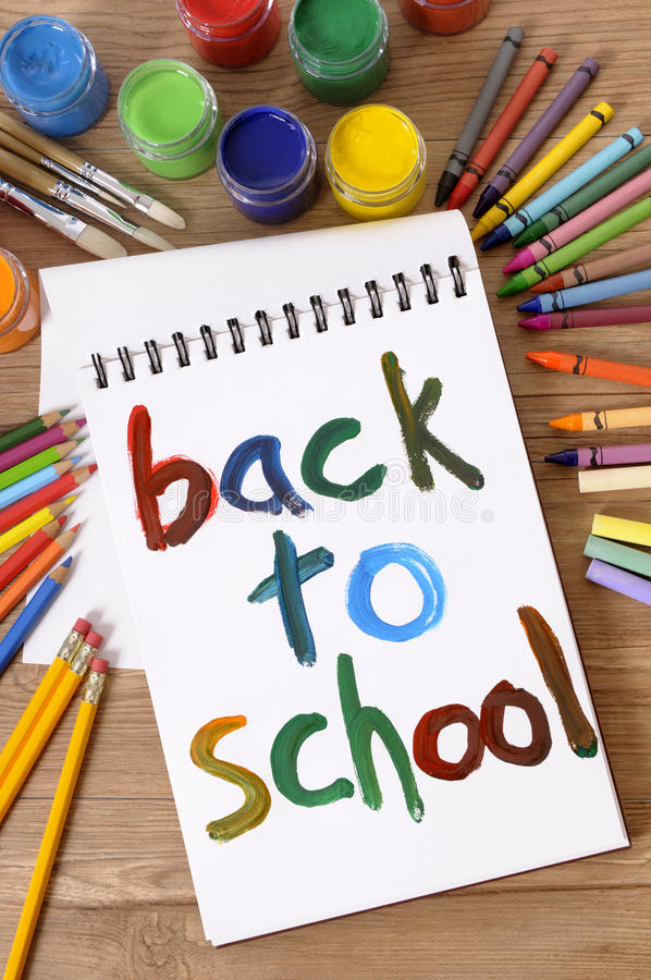 Back to school, vertical, art and craft class. The words Back to School painted on a white art book with various paints, crayons and pencils on a school desk stock photo