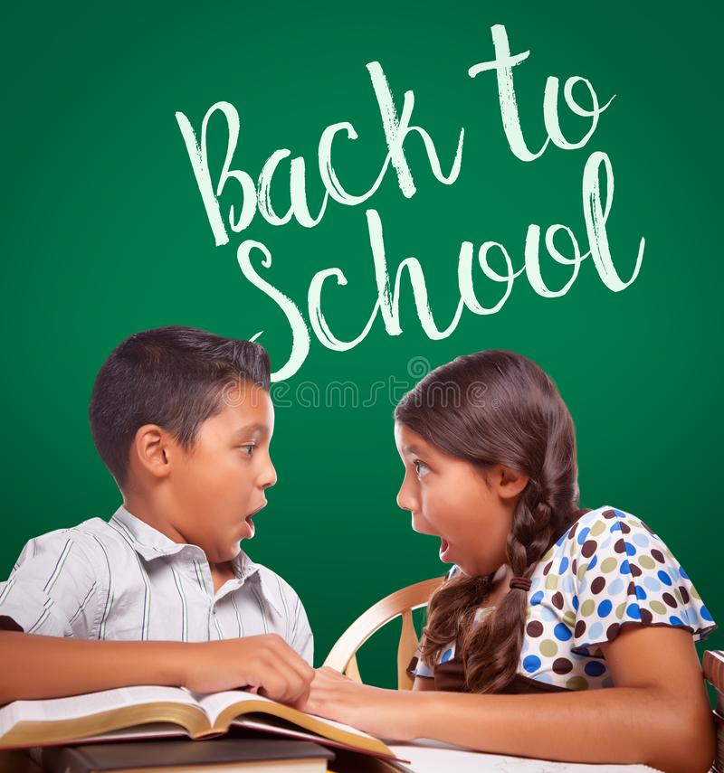 Back To School Written On Chalk Board Behind Hispanic Boy and Girl stock images