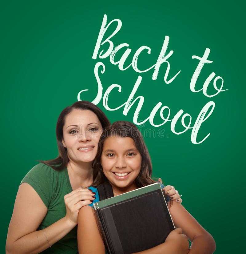 Back To School Written On Chalk Board Behind Proud Hispanic Mom stock photos