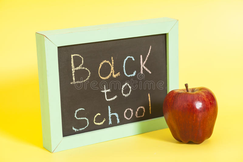 Back to School written on a chalkboard and red apple stock photos