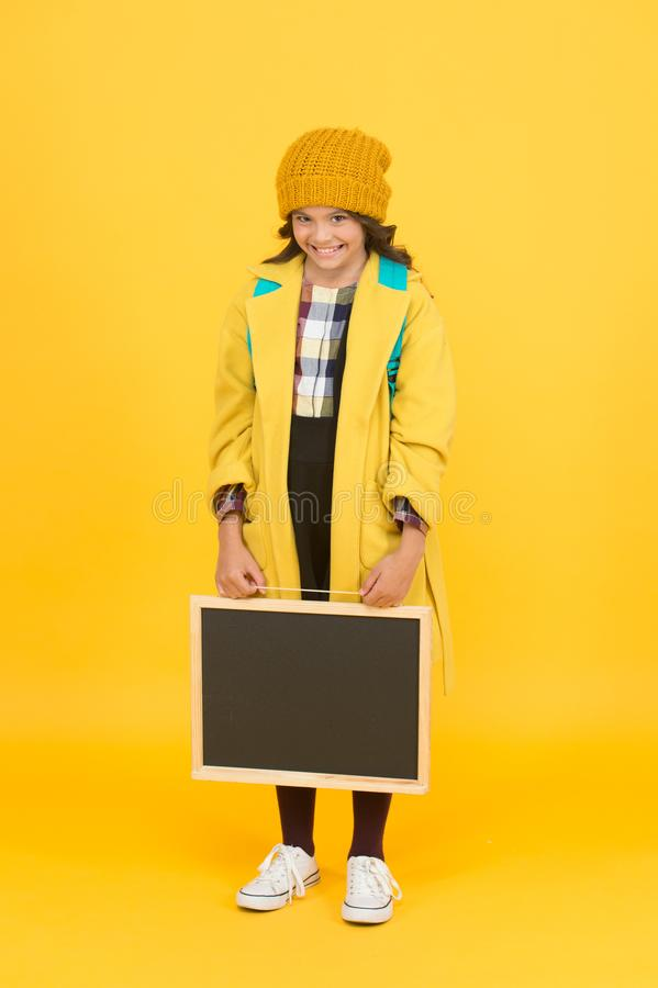 Back to student life. Little girl in school uniform on yellow background. Small child hold school blackboard back to royalty free stock photo