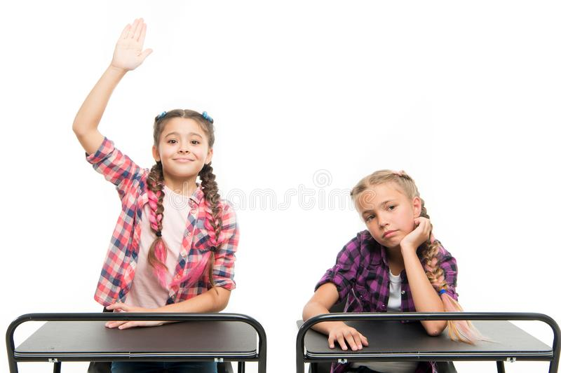 Back to their schooling. Adorable kids with raised hands sitting at desks isolated on white. Small schoolgirls having stock images