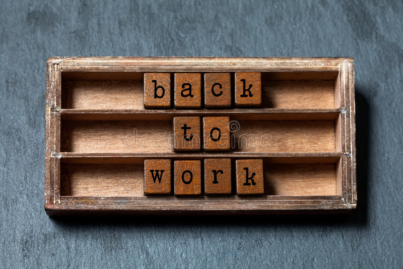 Back to work. Positive motivational quote. Vintage box, wooden cubes phrase with old style letters. Gray stone textured royalty free stock photos