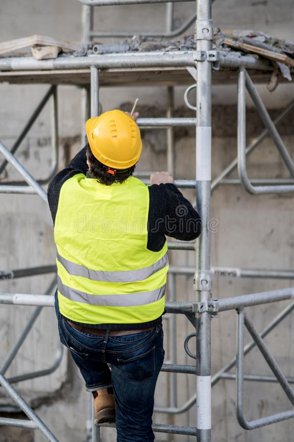 Back turned construction worker climbing a ladder stock photos