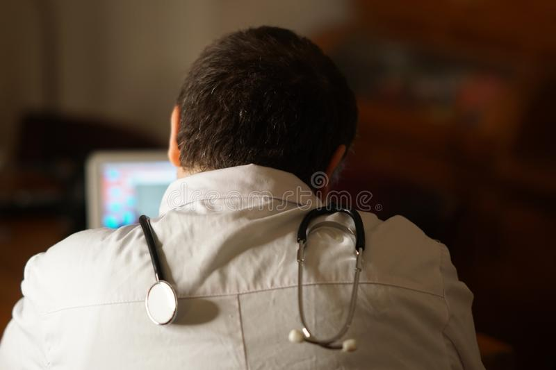 Back turned doctor sitting at his laptop royalty free stock photography