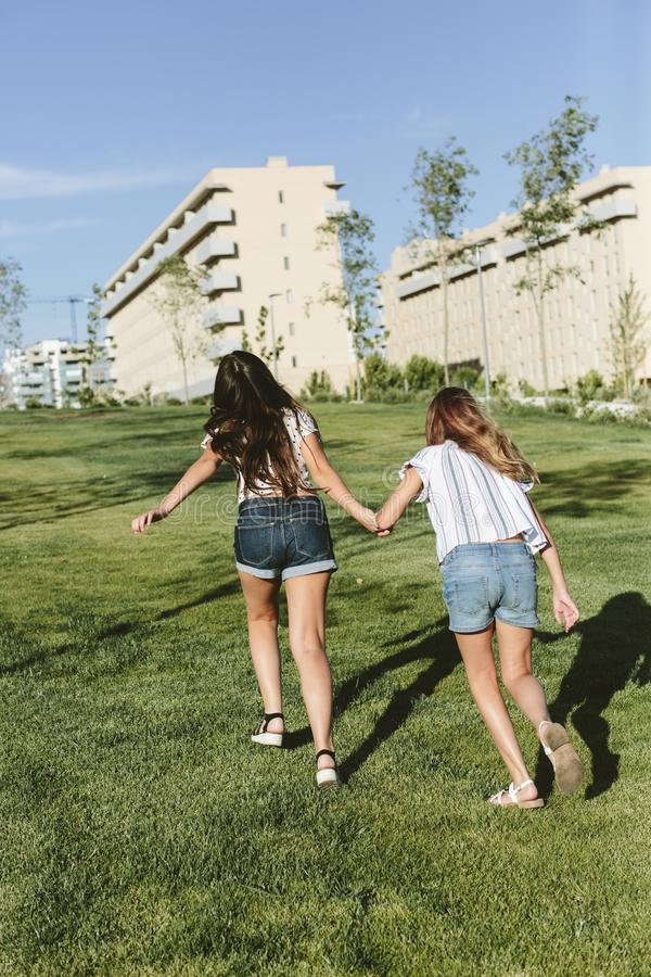 Back of two young girls running on a grass field. Back of two teenage girls running towards some buildings. They`re on grass field. They`re holding hands. They royalty free stock image