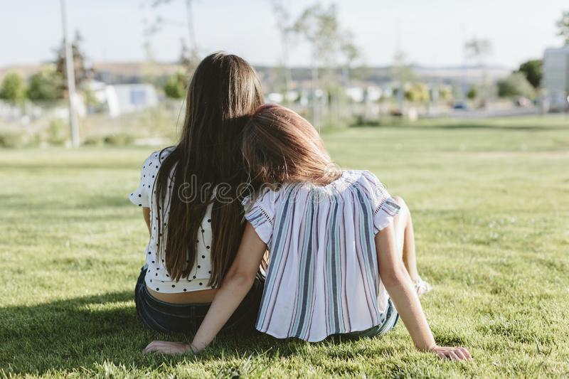Back of two young girls sitting on the grass. Back of two teenage girls with heads together. They`re sitting on the grass. They have long hair. They`re wearing royalty free stock photography