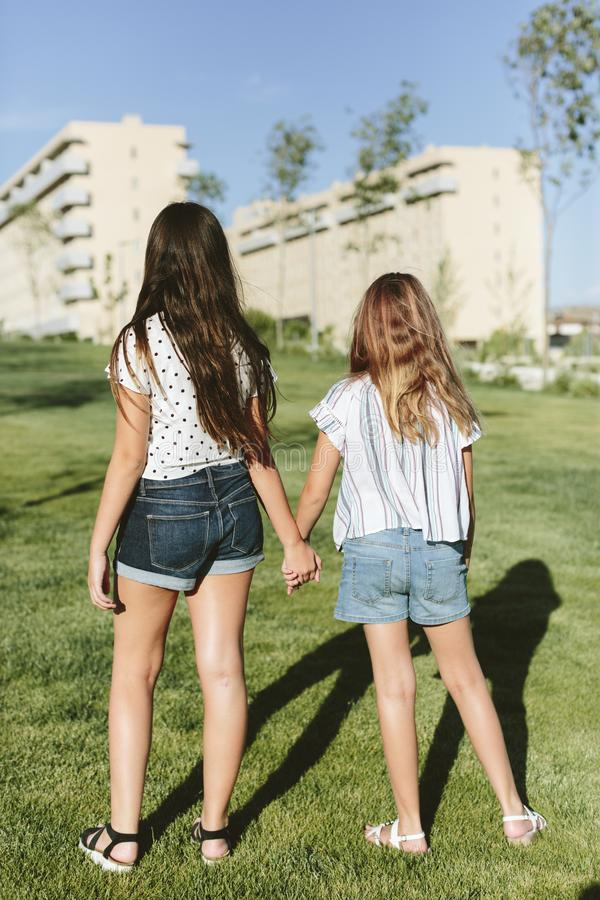 Back of two young girls standing on the grass. Back of two teenage girls looking at some buildings. They`re standing on the grass. They`re holding hands. They royalty free stock photos