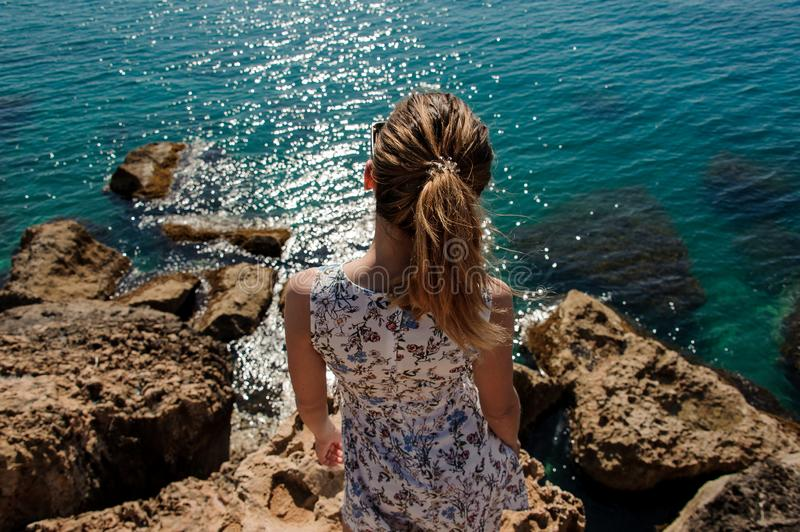 Back view from above young girl standing on the rock in dress royalty free stock photos