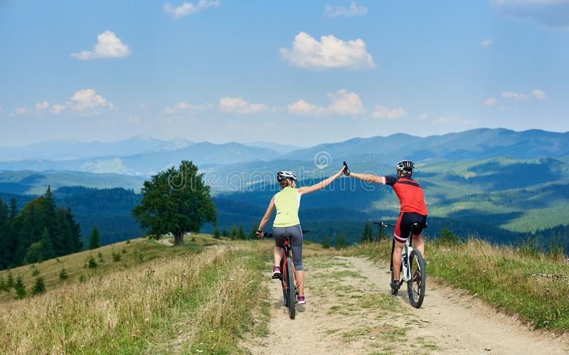 Back view of active couple cyclists in sportswear and helmets cycling down cross country bikes royalty free stock photography