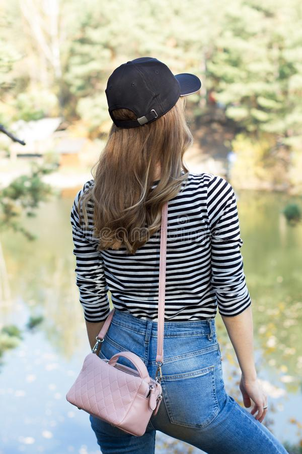 Back view of Active girl in a cap admires beautiful views of the mountains and forest - vertical image.  stock photography