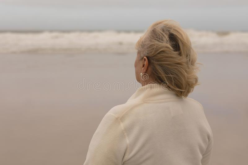 Senior woman standing at the beach royalty free stock image