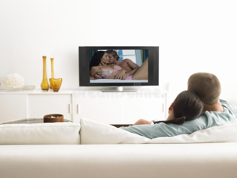 Back view of affectionate couple on sofa watching television royalty free stock images